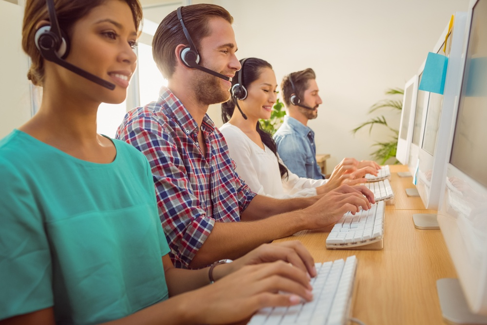 Business team working together at a call centre wearing headsets